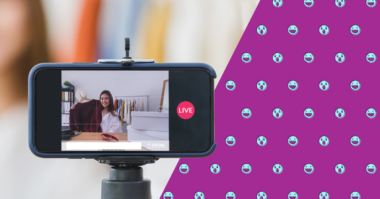 A phone, shown horizontal on a tripod, taking a live video of a girl who is holding up a red sweater.